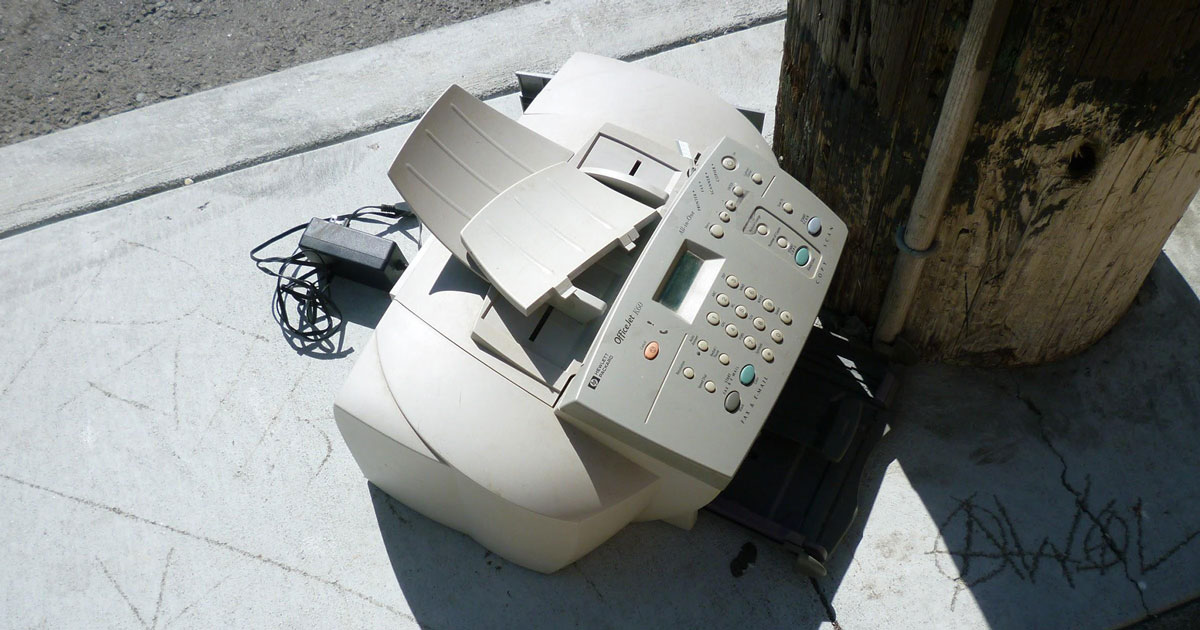 a fax machine left on a sidewalk broken